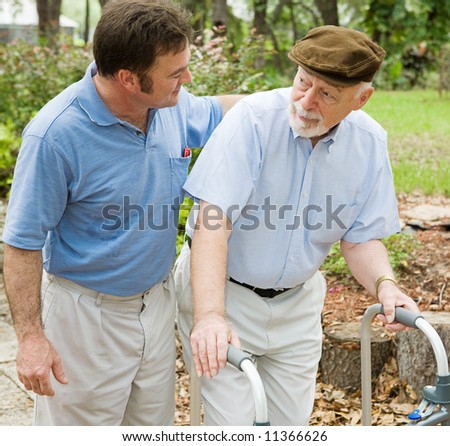 Adult son out for a walk with his father, who has alzheimers disease. - stock photo