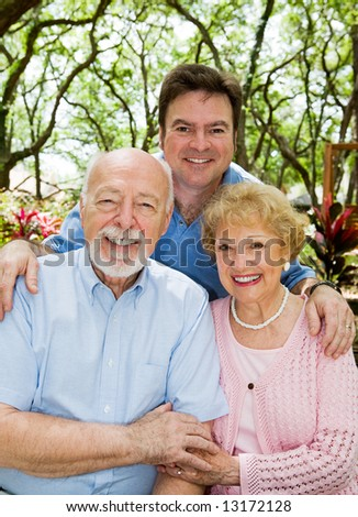 Adult son with his elderly parents outdoors in a natural setting.