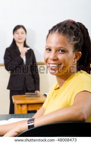 adult student in classroom, background is teacher standing by white board - stock photo