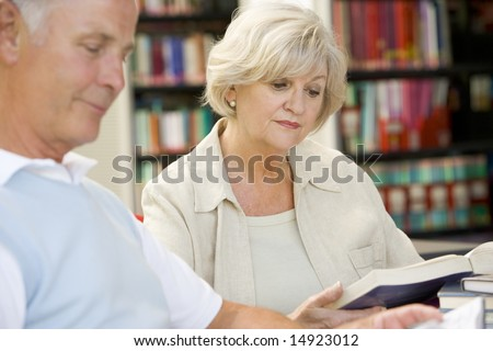 Adult students reading in a library - stock photo