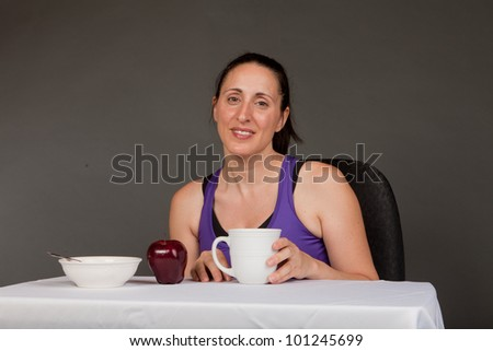 Adult sweating woman drinking a cup of coffee getting ready for breakfast - stock photo