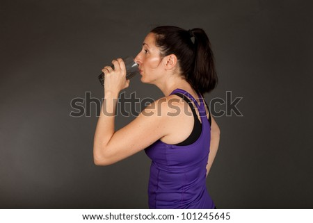 Adult sweating woman drinking a glass of water after a workout