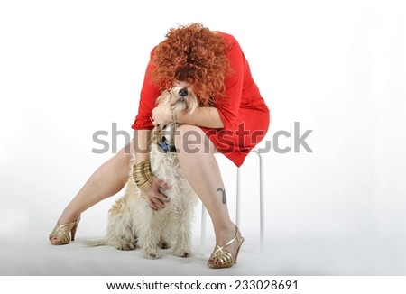Adult tattooed woman with red dress playing and kisses with her dog (spinone italiano) isolated on white background. - stock photo