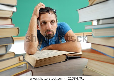 Adult teacher at a loss or thinking something. Photo adult man surrounded by books, education concept - stock photo
