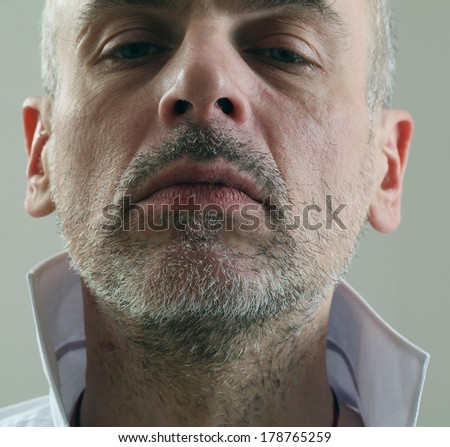 adult thin unshaven gray-haired man in a white shirt emotional