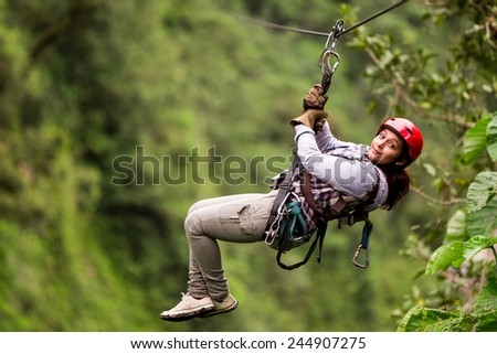 ADULT TOURIST WEARING CASUAL CLOTHING ON ZIP LINE TRIP, SELECTIVE FOCUS AGAINST BLURRED FOREST  - stock photo