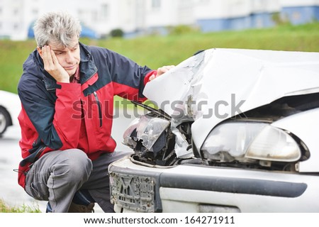 Adult upset driver man inspecting automobile body after crash car collision accident - stock photo