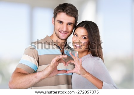 Adult. Valentine Couple. Portrait of Smiling Beauty Girl and her Handsome Boyfriend making shape of Heart by their Hands. Happy Joyful Family. Love Concept. Heart Sign. Laughing Happy Lovers - stock photo