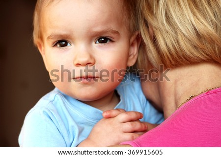 Adult white woman (grandmother) holding cute child boy who is hugging her and looking out behind her back, close-up emotional portrait, indoor - stock photo