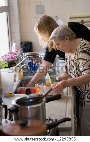 Adult woman and her elderly mother doing dishes at the kitchen sink together.