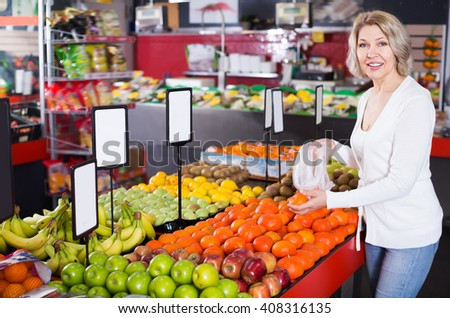 Adult woman choosing different fruits at farm food store display