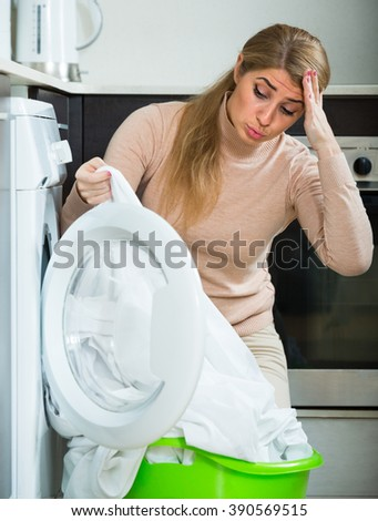 Adult woman displeased with washing quality of linen after laundry at home