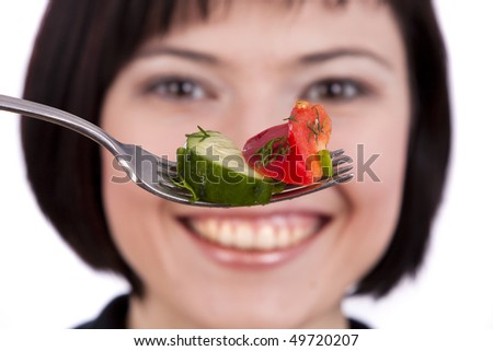 Adult woman holding fork with healthy salad. Portrait of young happy female eating salad - stock photo