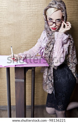 adult woman in a headscarf writes a pen on paper - stock photo