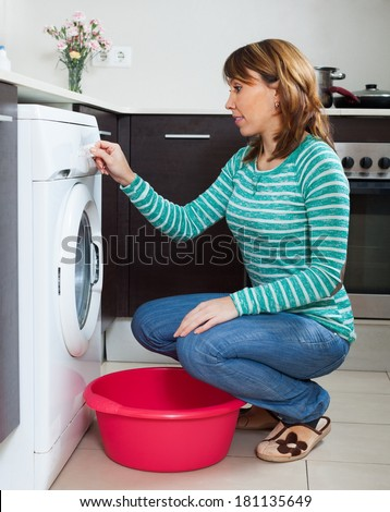 Adult woman in green doing laundry with washing machine at home