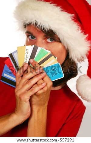 adult woman in Santa Hat hiding behind handful of credit cards (Holiday spending and debt) - stock photo