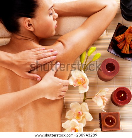 Adult woman in spa salon having body relaxing massage.  - stock photo