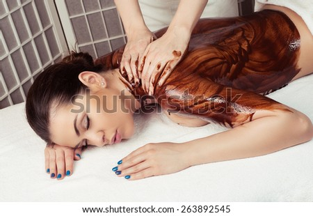 Adult woman in spa salon having body relaxing massage, lying on table, with chocolate olive - stock photo
