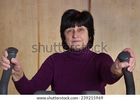Adult woman is training by exercise bike. - stock photo
