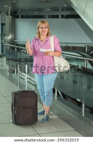 Adult woman is traveling. Woman with suitcase standing in the building bus station or airport. Holding her passport and ticket. Retired woman embarks on a journey with his travel luggage. Thumbs up.