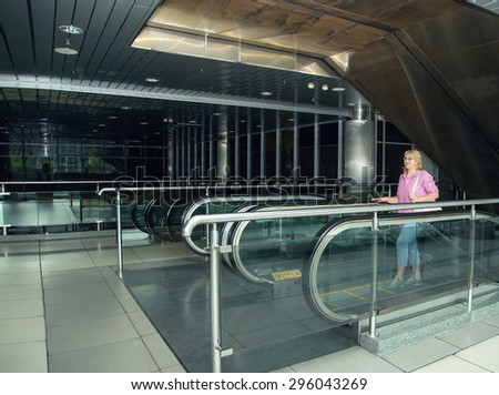 Adult woman is traveling. Woman with suitcase standing in the building bus station or airport. She is holding her passport and ticket. Retired woman embarks on a journey with his travel luggage. - stock photo