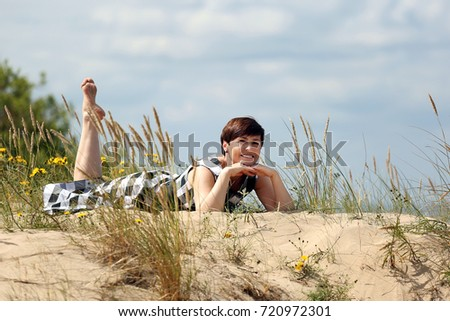 Adult woman lies on sand dune - rest on beach