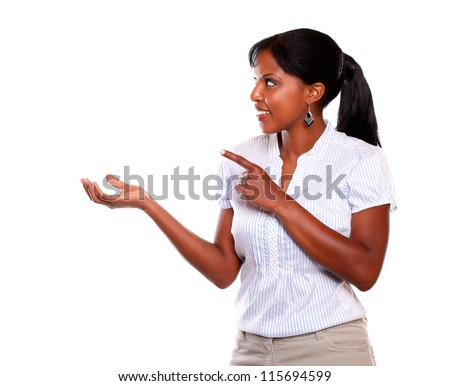 Adult woman looking and pointing to her right against white background - stock photo