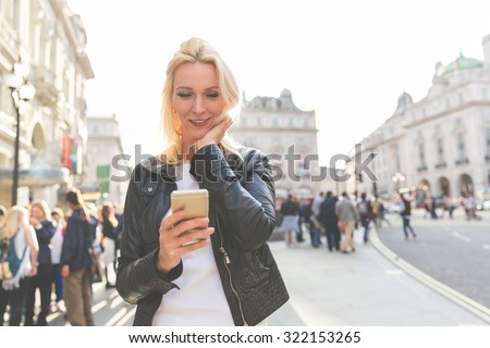 Adult woman looking at smart phone in London at sunset. She is a blonde woman on her early forties, she looks candid and spontaneous. Backlight shot with blurred people on background. - stock photo