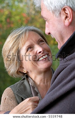 Adult woman looks at her husband and smiles. Focus on the woman. - stock photo
