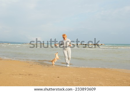 Adult woman on the background of the sea playing with the dog. Senior woman in tracksuit enjoying life. Fitness and walking outdoors near the sea and the beach. Lifestyle adult retired. - stock photo
