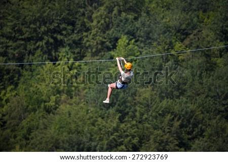 Adult woman on zip line - stock photo