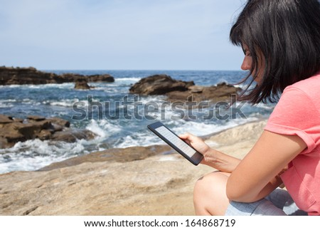 Adult woman over the Atlantic coast with e-book - stock photo