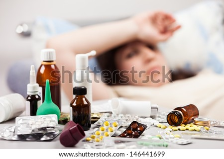 Adult woman patient with high temperature lying down bed for cold and flu illness relief - stock photo