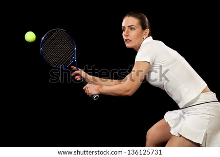 Adult woman playing tennis. Studio shot over black.
