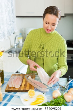 adult woman preparing slices of white fish for baking