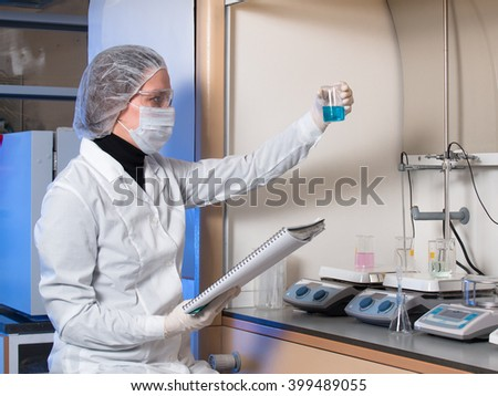 Adult woman protective glasses and medical mask holding in his hand glass flask with blue liquid and in the other hand she is holding a syringe against the background of medical equipment for research
