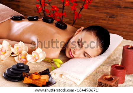 Adult woman relaxing in spa salon with hot stones on back. Beauty treatment therapy - stock photo
