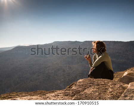 Adult woman sitting on a sky background