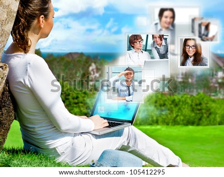 Adult woman sitting under tree on green grass and communicating with her team or clients or partners. Work where you want and e-business concept.