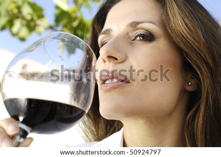 Adult woman smelling wine - stock photo