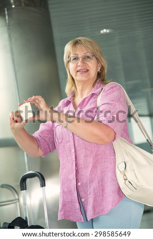 Adult woman smiling and talking on a smart phone. Happy woman her cell phone. Traveler with mobile phone in airport. Tourist woman with travel bag. Take photos on your mobile phone. - stock photo