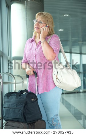 Adult woman smiling and talking on a smart phone. Happy woman holding her cell phone. Traveler with mobile phone in airport. tourist Woman with travel bag and talking cell phone.  - stock photo