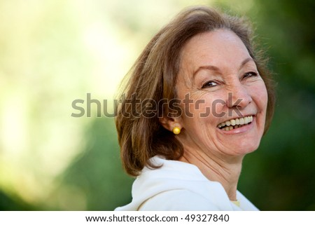 Adult woman smiling outdoors looking very happy