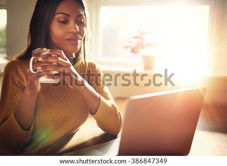 Adult woman smiling sitting near bright window while looking at open laptop computer on table and holding white mug - stock photo