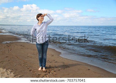 Adult woman stands looking into distance on beach near blue sea