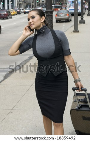 Adult woman talking on cell phone while looking for a cab on a sunny day - stock photo