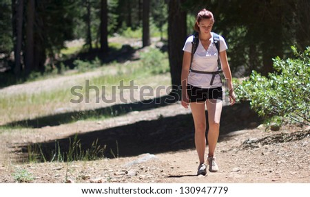 Adult woman wearing shorts and t-shirt hikes through woods - stock photo
