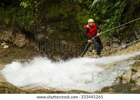 Adult Woman Wearing Waterproof Equipment Descending A Waterfall - stock photo