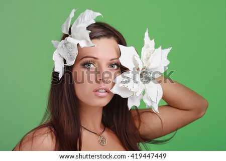 Adult woman with beautiful face and white flowers. Skin care concept on a green. - stock photo