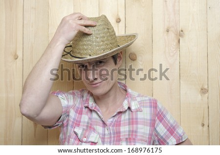 adult woman with cowboy hat leaning against a wooden wall - stock photo